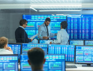 Men in stock trading room surrounded by ticker monitors